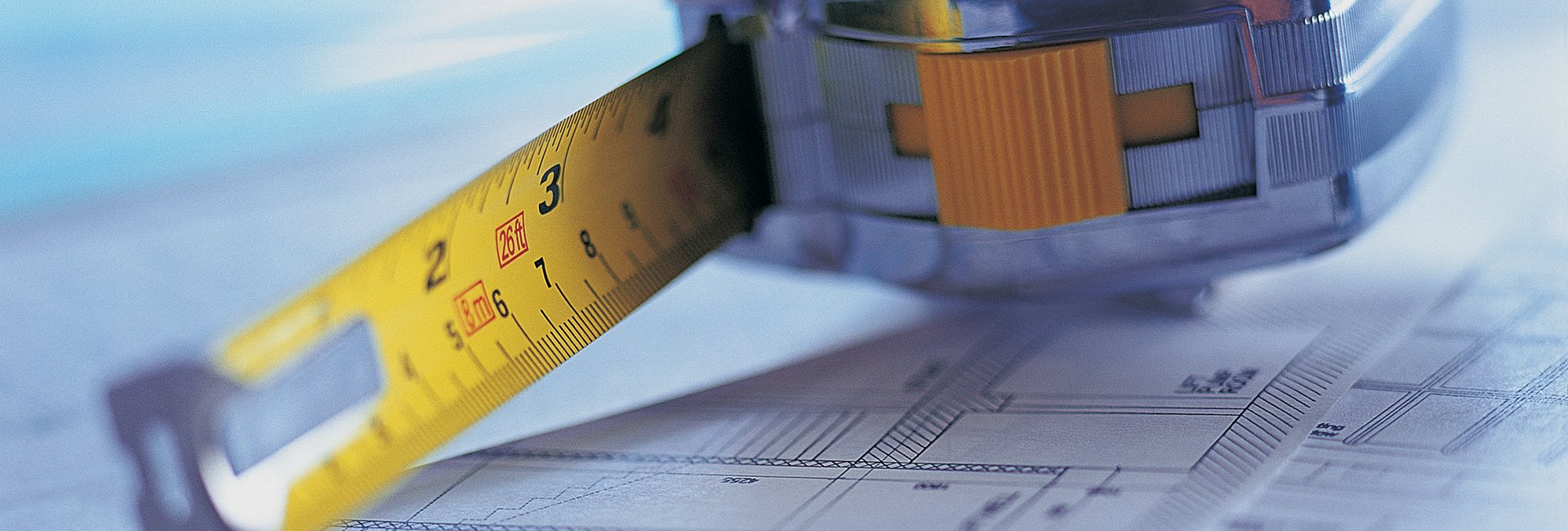 Yellow and silver tape measure on top of architects building plans