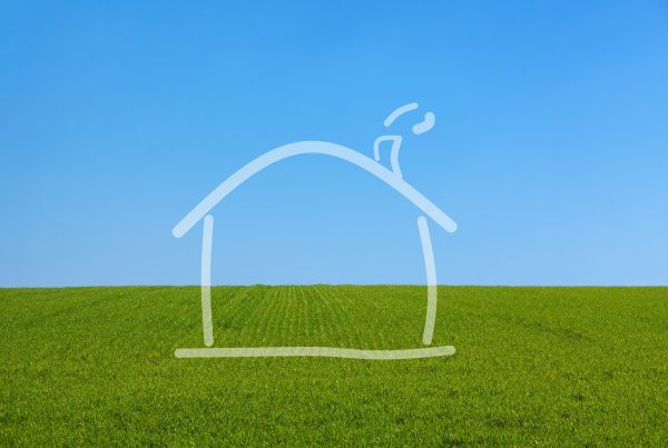 Outline of a house on a background of green grass and blue sky