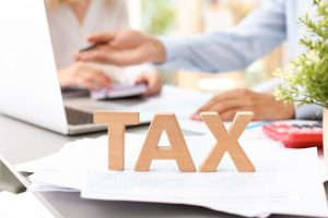 Word TAX and blurred accountants on background