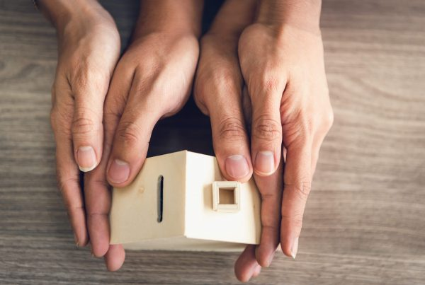 Couple Hands Holding Housing Model for Future Real Estate Saving, People Hand Joint to Protection Home Property Togetherness. House Insurance and Residential Loan Investment Concept.