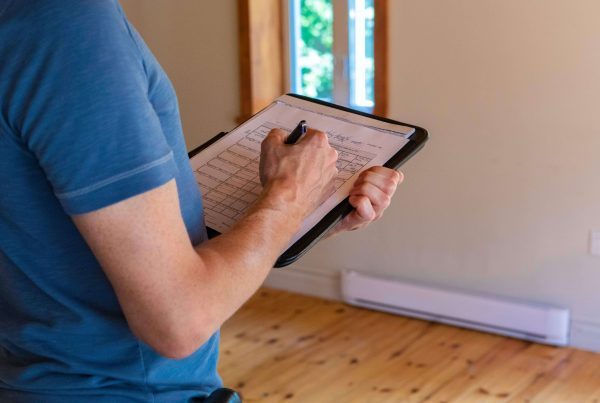 A close up view on the muscular arm of a professional man wearing a short sleeved blue shirt, filling out papers during a home inspection