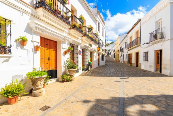 Narrow street with houses in white Andalusian village with typical Spanish architecture, Zahara de la Sierra, Spain